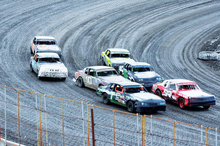 Garrick Hodge/MDN Several cars fight for position during a heat race Sunday at Nodak Speedway in Minot.