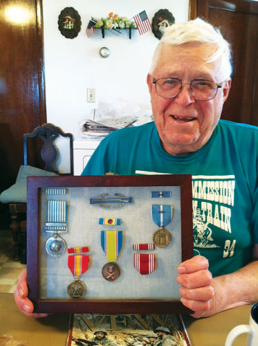 Submitted Photo Korean War veteran Ernie Hoelscher holds a case containing two Bronze Stars, a United Nations Medal and numerous other medals earned for his military service between 1952-1954.
