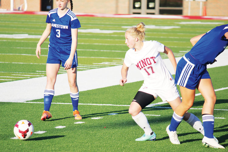 Alex Eisen/MDN Minot High senior Emily Love (17) dribbles past a Jamestown defender in a WDA game played on May 5 at Herb Parker Stadium.