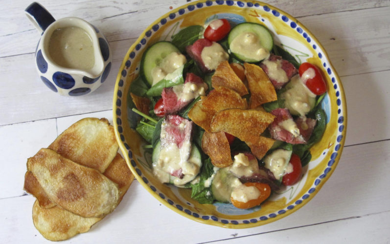 This May 20, 2017 photo shows a warm steak and potato chip salad with blue cheese dressing in New York. This dish is from a recipe by Sara Moulton. (Sara Moulton via AP)