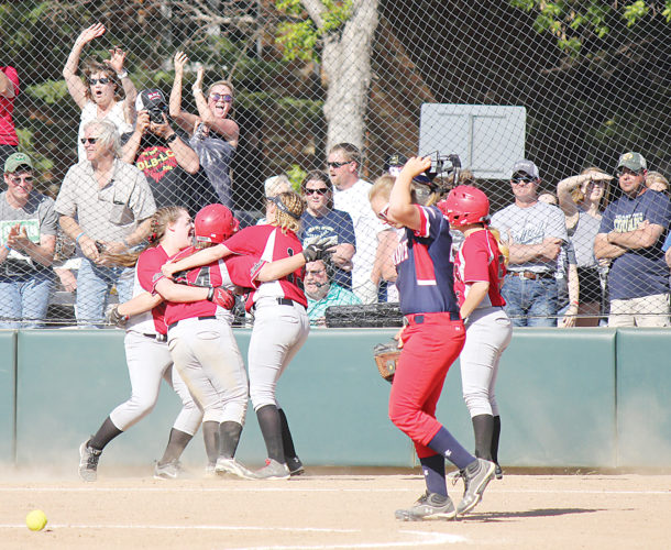 Alex Eisen/MDN Three Des Lacs-Burlington/Lewis & Clark players celebrate, as Patriots' Dallas Jorgensen walks by, after the winning run was scored for the Lakers in a 6-5 victory over May-Port-C-G in the first round of the Class B softball state tournament in Jamestown.