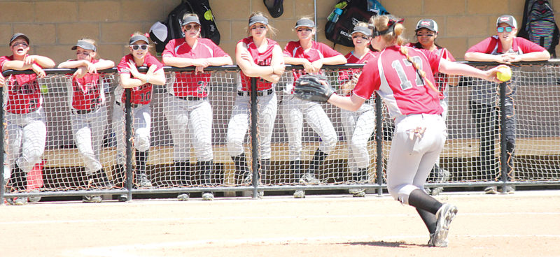 Alex Eisen/MDN Eighth grader Brooklyn Benno (17) throws a pitch with her Des Lacs-Burlington/Lewis & Clark teammates watching on from the dugout in the third-place game at the Class B state softball tournament in Jamestown.