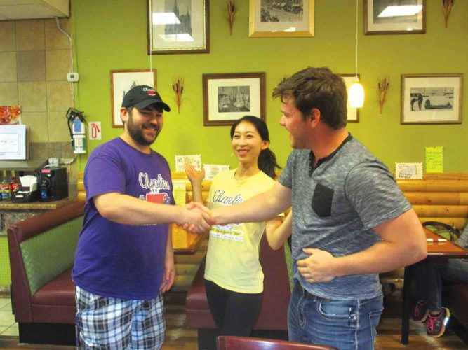Allan Blanks/MDN  Brandon Yabusaki, left, and Tiffany Lee congratulate Cole Anderson, as the new speed-eating champion at Charlie's Main Street Cafe, Thursday afternoon.