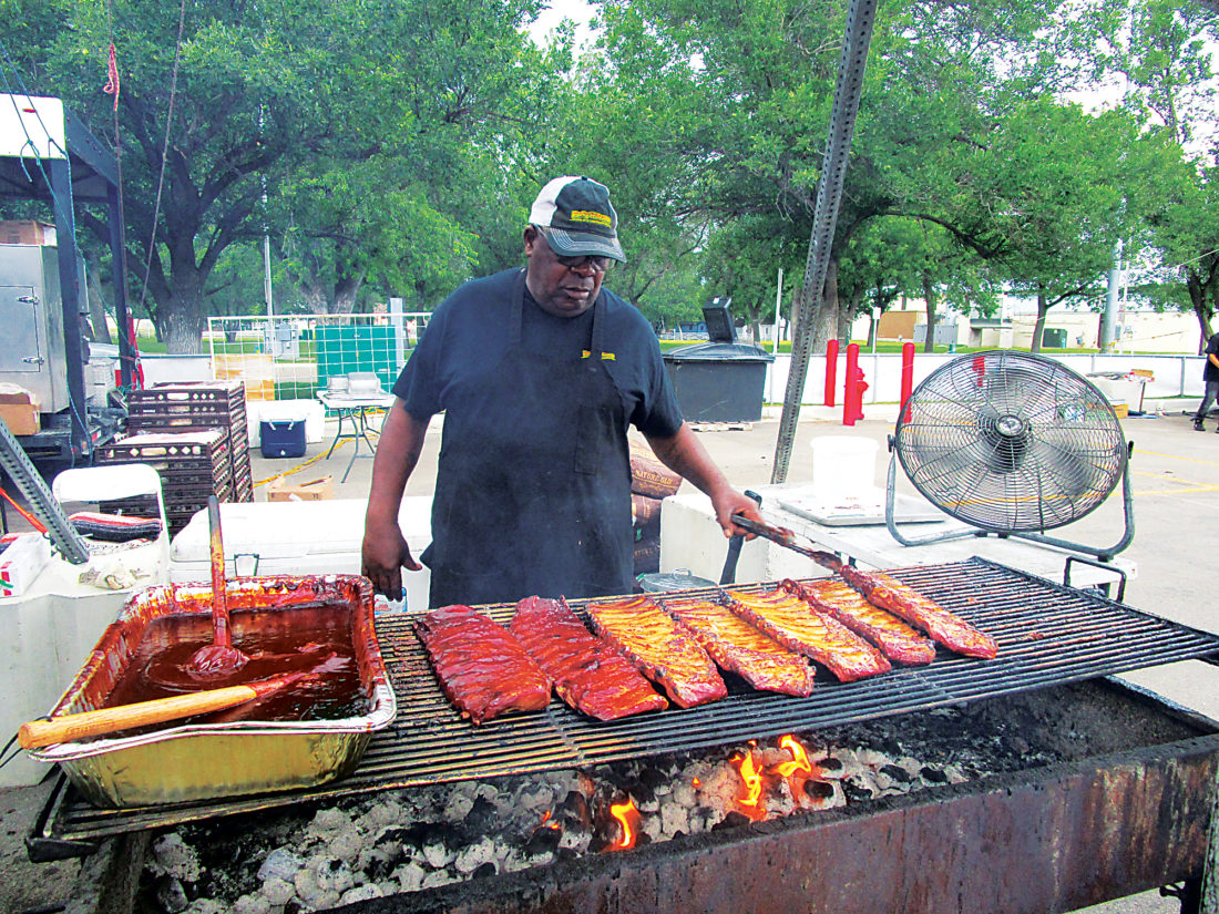 Allan Blanks/MDN Cornell Simon, a grill master at the awarding-winning Porky-N-Beans B-B-Q Company, flips tender slabs of ribs at Minot's third annual Ribfest Saturday afternoon.