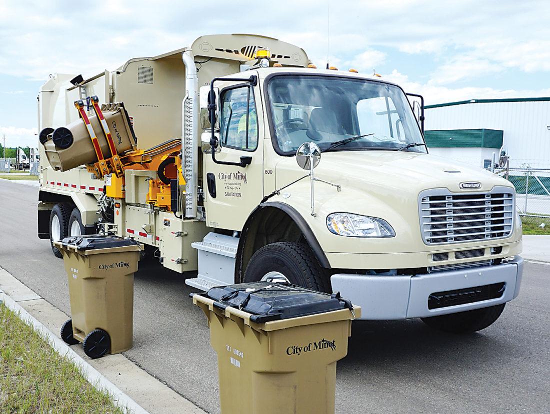 Jill Schramm/MDN A sanitation worker runs a new Minot garbage truck through a practice course at an industrial park in east Minot Wednesday.