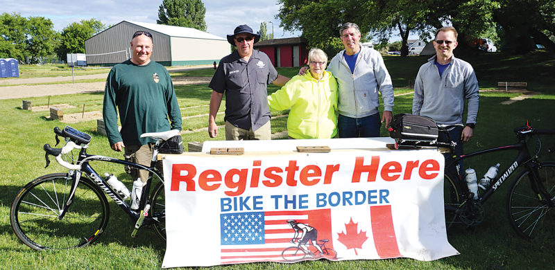 Jill Schramm/MDN Cyclists Virgil Borman and Jason Durick, sag team members Janet Cron  and Jim Conklin and cyclist David Orem, from left, spend Saturday evening at the Bike the Border headquarters and campground at the Burlington Sports Complex.