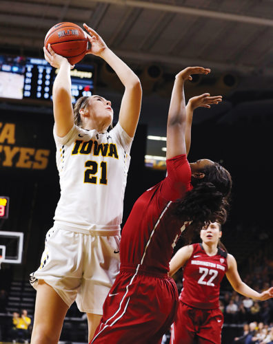 Submitted Photo Iowa sophomore Hannah Stewart (21) attacks the rim in a WNIT tournament quarterfinals game against Washington State on March 26. Photo courtesy of Brian Ray/hawkeyesports.com.