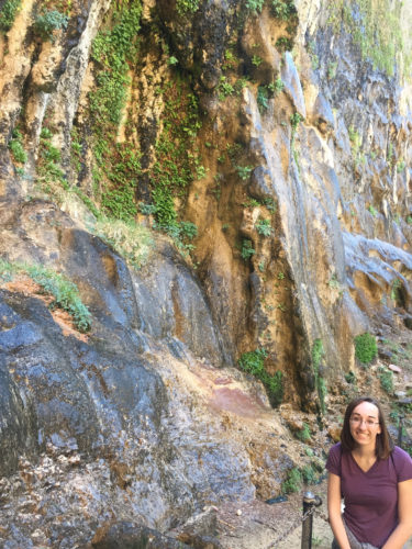 This May 26, 2017 photo shows Kelsey Delehanty in front of Weeping Rock, the hanging gardens created by dripping streams, at Zion National Park in Utah. Weeping Rock is one of nine shuttle bus stops along Zion Canyon Scenic Drive, which is closed to private cars between March and November. (AP Photo/Eva Parziale)