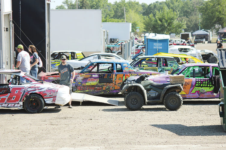 Alex Eisen/MDN Drivers and their crew prepare in the pits for racing at Nodak Speedway on July 4.