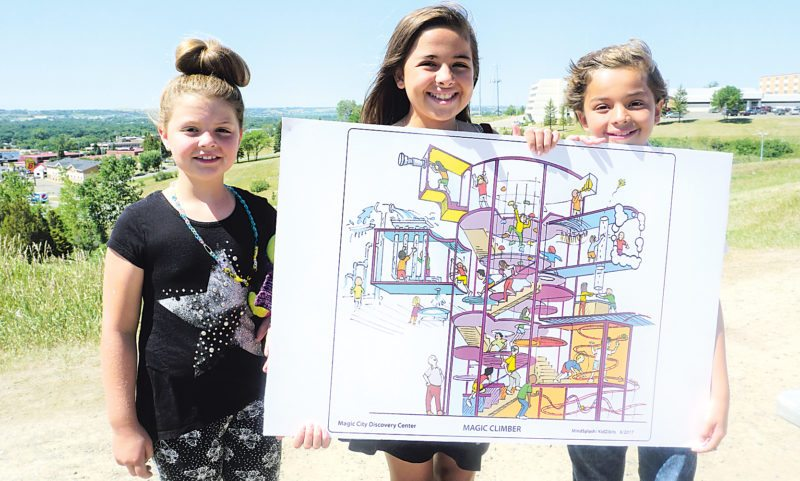 Jill Schramm/MDN Sydney Lyman and Sholeh and Shayan Mozaffari hold an architect's rendering of an interactive exhibit proposed for a new Minot Discovery Center at a news conference Thursday.
