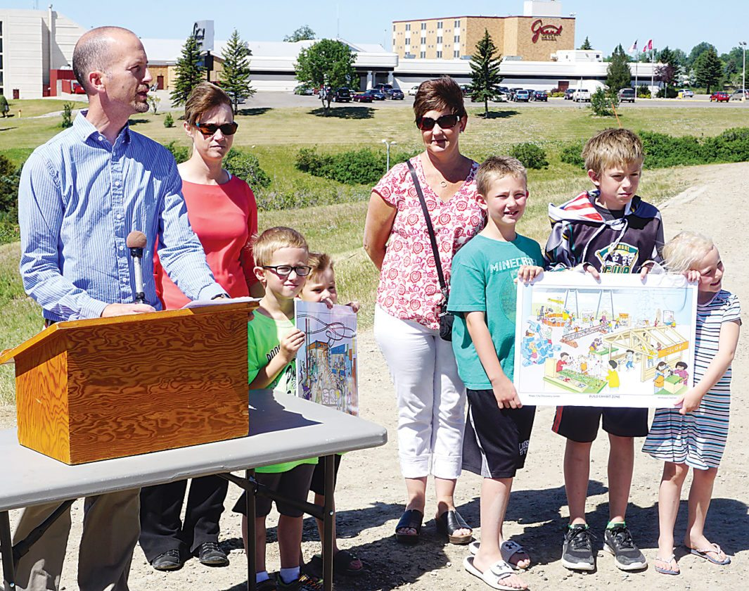 Jill Schramm/MDN Mark Lyman, left, spokesman for the Minot Children's Museum, announces plans for a new museum center on the proposed site in north Minot while joined by other board members and supporters.