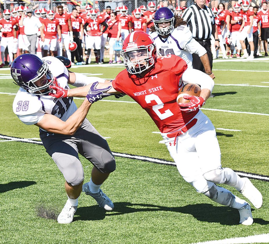 Garrick Hodge/MDN Minot State's Ryan Fila (2) stiff arms University of Sioux Falls defensive back Austin Schaffer (38) during an NSIC football game last season at Herb Parker Stadium in Minot. The Beavers hope to build on their three conference victories a season ago.