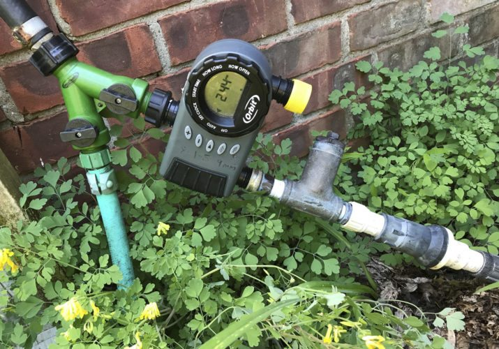 This June 26, 2017 photo shows the beginning portion of a drip irrigation system at a home in New Paltz, N.Y. Watering with drip irrigation has many benefits, not the least of which is that it is easily automated by merely setting a timer. The timer is pictured here along with the filter and pressure reducer that starts water off in any drip irrigation system. (Lee Reich via AP)