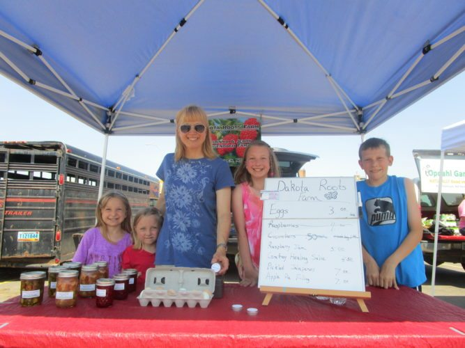 Molly, left, Abby, AriAnna, Kelsey and Austin Wingenbach of Dakota Roots Farm, enjoyed tremendous success during day one of the 2017 North Prairie Farmers Market in downtown Minot. Within two hours, Dakota Roots Farm was sold out of cucumbers.  Allan Blanks/MDN
