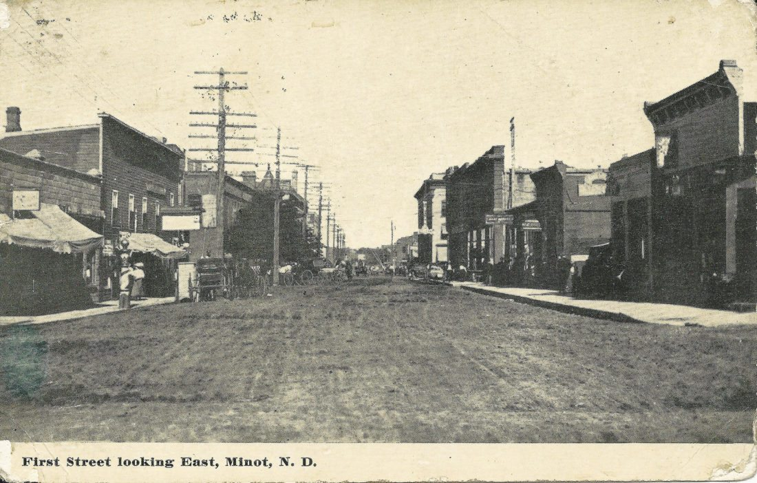 File Photo An early day postcard carries a photo of Minot's First Street looking east.