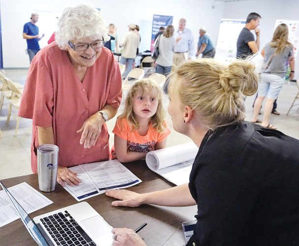 Jill Schramm/MDN Sharon Melland, with her great-granddaughter Aaliyah, talks with Laura Horner, mapping coordinator with the State Water Commission at an informational event in Sawyer Monday.