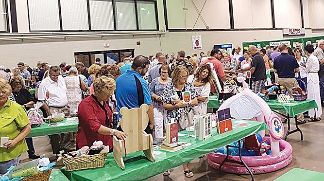 Submitted Photo Guests at the Great Tomato Festival explore a combination of cook books, gift baskets and menu which consists of smoked pork chops cooked to perfection by master chefs, a top secret recipe of roasted tomatoes stuffed with rice,along with chips and salsa, tomato and cucumber salad, beer batter bread and brownies. The 29th annual Great Tomato Festival will be held on Aug. 9, at the North Dakota State Fair Center, 4H Hall, 2005 Burdick Expressway East.