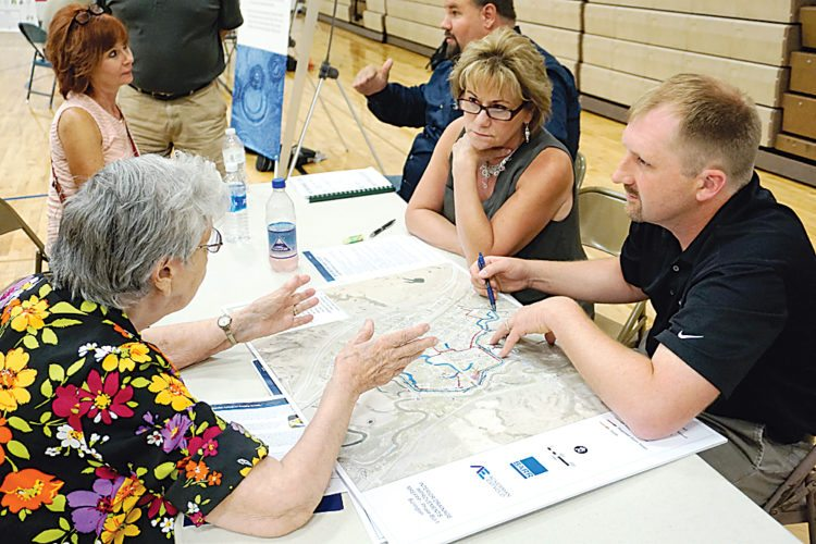 Jill Schramm/MDN Burlington City Auditor Diane Fugere and city engineer Patrick Samson review a flood plain map with a resident at a FEMA flood map informational event in Burlington Tuesday.