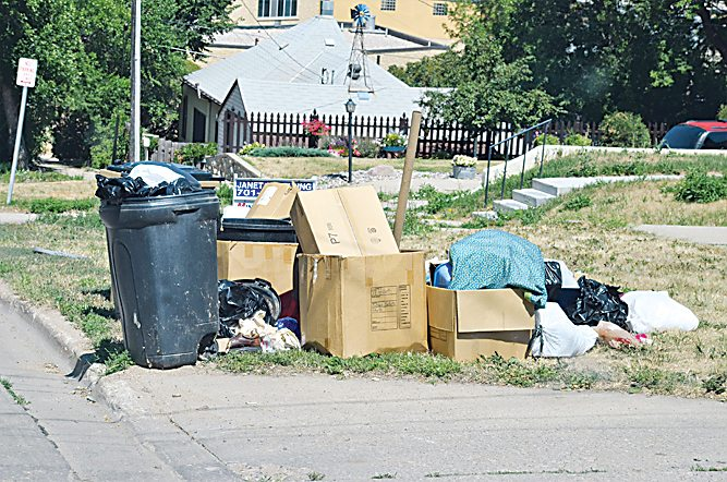 Eloise Ogden/MDN A garbage cart is hidden Wednesday behind other trash left out in southeast Minot for the city collection service. The city has been collecting all garbage during the first week of automated collection but will be moving to garbage cart use only.