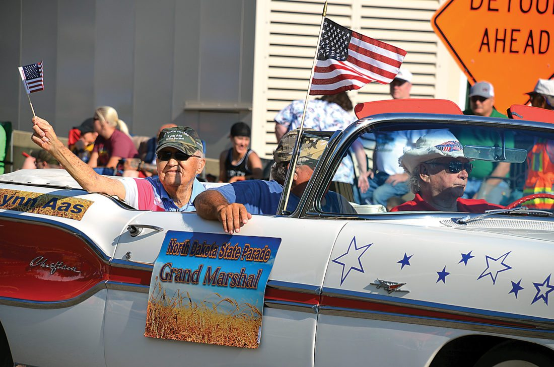 Eloise Ogden/MDN World War II veteran Lynn Aas, 96, of Minot, grand marshal of the North Dakota State Fair Parade, waves a flag as he passes by the crowd watching the parade on Burdick Expressway Saturday morning. Family members rode with him in a vehicle owned and driven by Vance Castleman of Minot. Other family members walked behind the vehicle. Aas recently received France's highest honor, the Knight of the Legion Honor medal, a medal paying tribute to the soldiers who did so much for France and Western Europe.