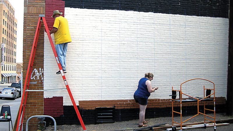 Andrea Johnson/MDN Tim Knickerbocker and Courtney DuPona paint a mural on the wall of the Mouse River Players Building in downtown Minot on Saturday morning.