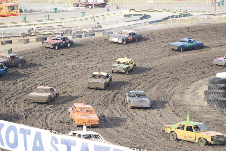 Garrick Hodge/MDN Several race cars round the corner at Nodak Speedway trying to navigate a muddy track during the North Dakota State Fair enduro race on Monday in Minot.