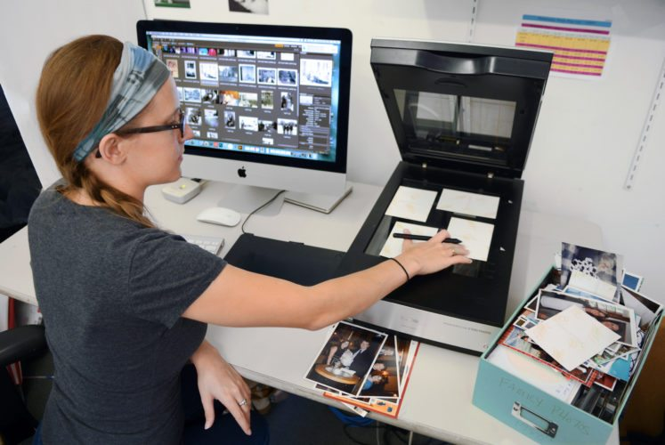 In this July 18, 2017 photo, imagining specialist Erin McClintic works in the lab at Phototronics in Winnetka, Ill., digitizing and archiving a shoebox of customer photographs, right. (Phototronics via AP)