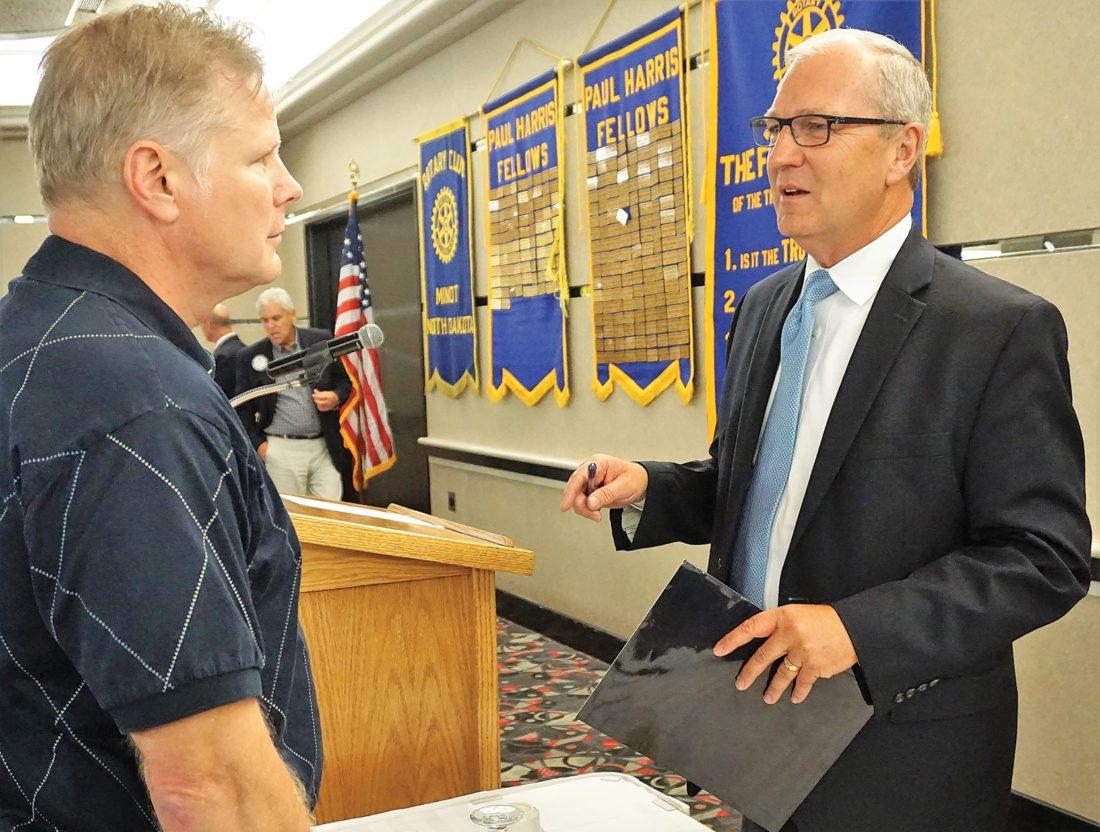 Jill Schramm/MDN Congressman Kevin Cramer speaks with Matt Watne following a Rotary Club meeting in Minot Monday.