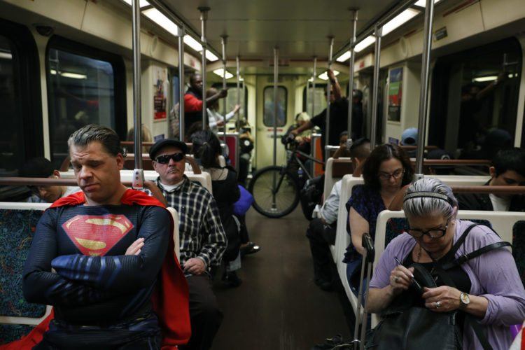"""In this Tuesday, May 16, 2017 photo, superhero impersonator Justin Harrison, left, rides a Metro train wearing a Superman costume on his way to Hollywood Boulevard in Los Angeles. """"I always go out in a costume,"""" said Harrison. """"I love seeing people happy and seeing them smile."""" (AP Photo/Jae C. Hong)"""