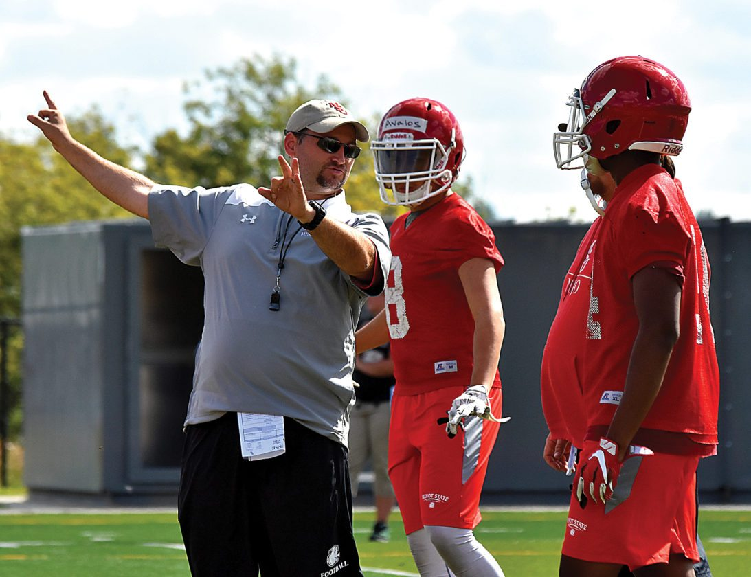 Garrick Hodge/MDN  Minot State head coach Mike Aldrich, left, goes over a coverage assignment with a few of his players.