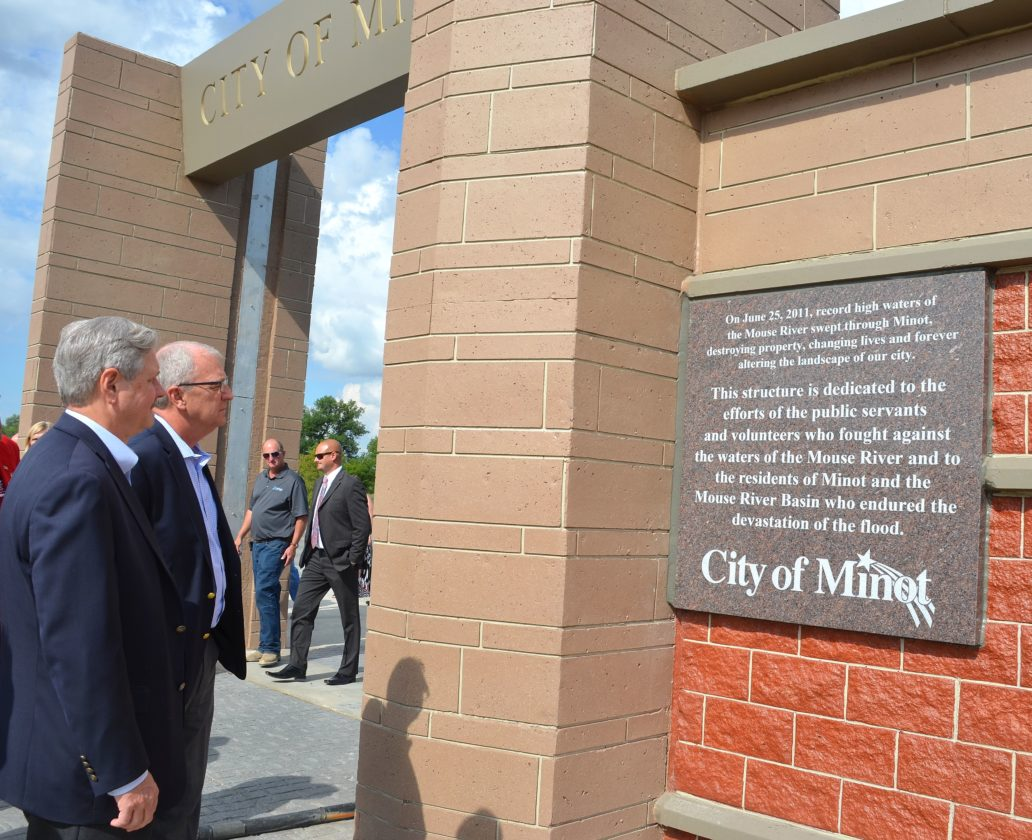 Eloise Ogden/MDN Sen. John Hoeven, left, and Congressman Kevin Cramer read a plaque on the floodwall east of the Minot Water Treatment Plant Friday. A ceremony was held to dedicate the Hazard Mitigation Grant Program-Water Treatment Plant flood protection project. The finished project features the first floodwalls built in the Minot community.