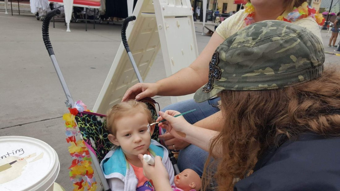 Submitted Photo Mckenzie Sabo paints a rainbow on one of her customers at the Festival on Main.