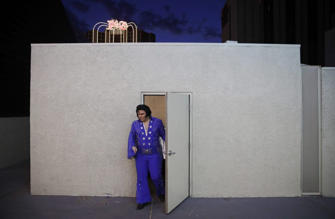"In this Aug. 6, 2017, photo, Tyler James leaves a dressing room before performing as Elvis on Fremont Street in Las Vegas. For James it isn't just the music that draws him to perform as Elvis. ""He always gave back to his fans... he cared about people."" (AP Photo/John Locher)"
