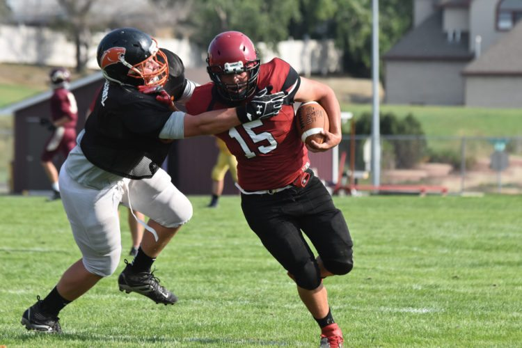 Garrick Hodge/MDN Nedrose's Duncan Pryor (15) stiff arms a Rugby defender in a scrimmage held Thursday at Duane Carlson Stadium in Minot.
