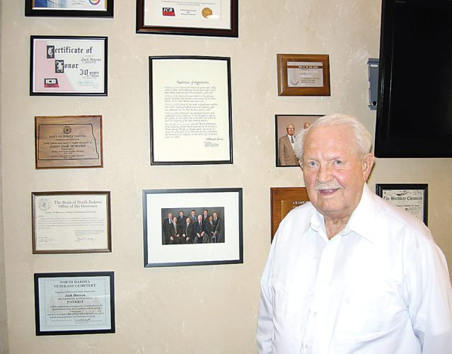 File photo Jack Hoeven stands next to a wall of citations received over the years in July 2014 as First Western Bank & Trust was celebrating its 50th anniversary.