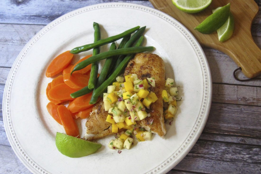 This Aug. 9. 2017 photo shows spicy sauteed fish with a pineapple mango salsa in New York. This dish is from a recipe by Sara Moulton. (Sara Moulton via AP)