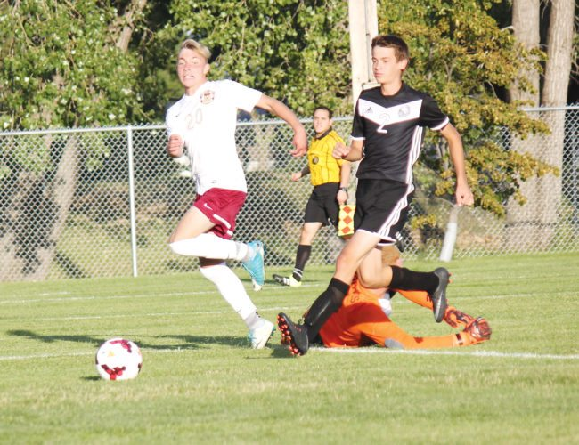 Alex Eisen/MDN Minot High sophomore Noah Schmidt (20) slots in Minot's first goal of the game Tuesday against Mandan.