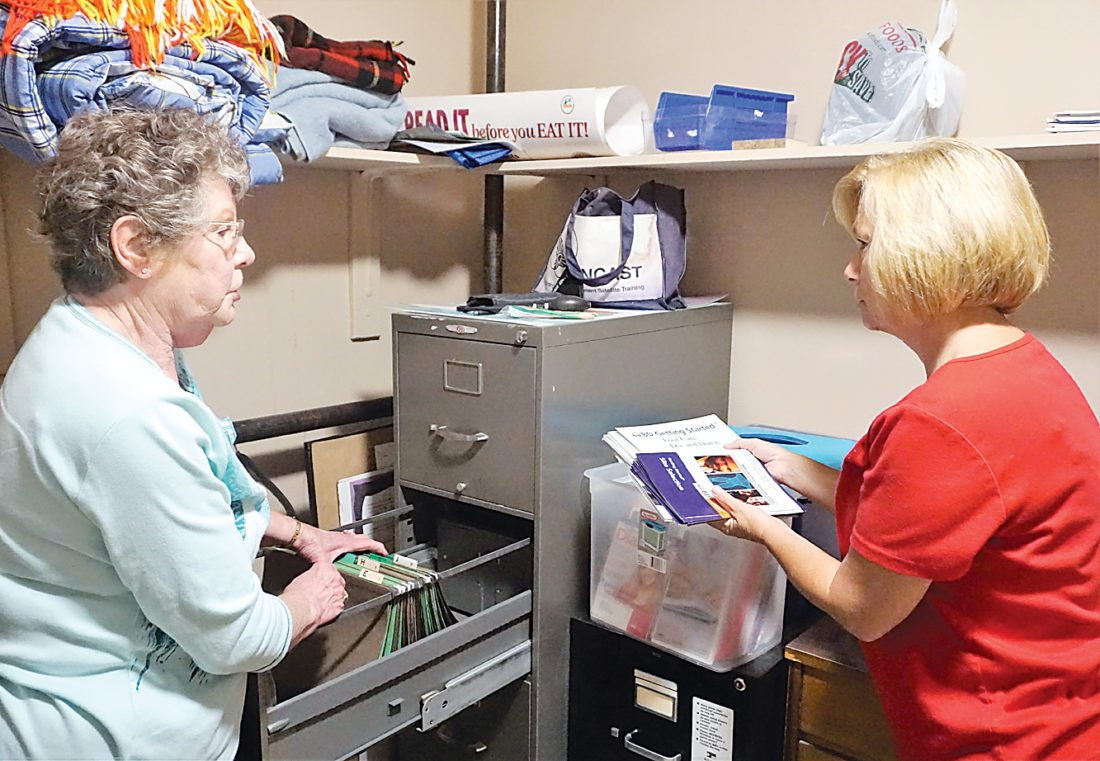 Jill Schramm/MDN Clarice Purdy, a volunteer at City & Country Health Clinic since it opened in 1999, and volunteer Kelly Thom go through patient files to be shredded and brochures to be recycled in cleaning out the clinic Thursday.