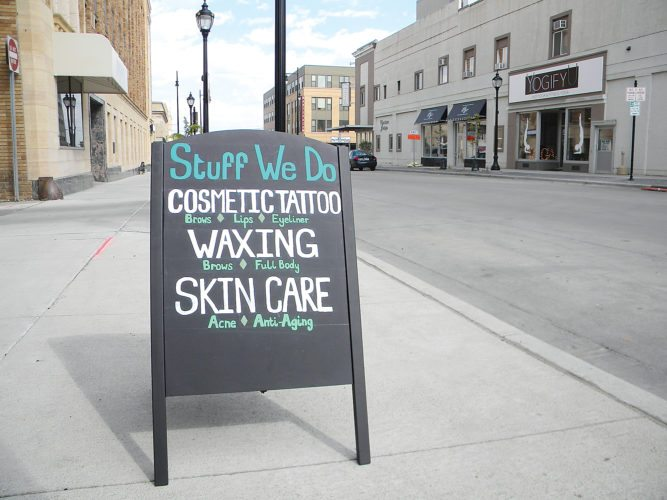 Kent Olson/MDN A sidewalk sign calls attention to some of the services available at Nickel & Dodge, 14 West Central Ave.