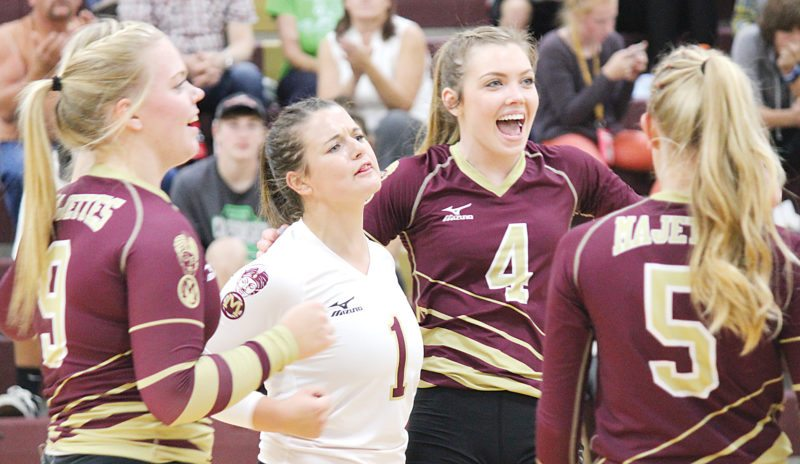 Alex Eisen/MDN Minot High seniors Rylee Terrel (1) and Elise Klein (4) celebrate after scoring a point Tuesday in a match again Mandan. The Majettes lost in five sets.