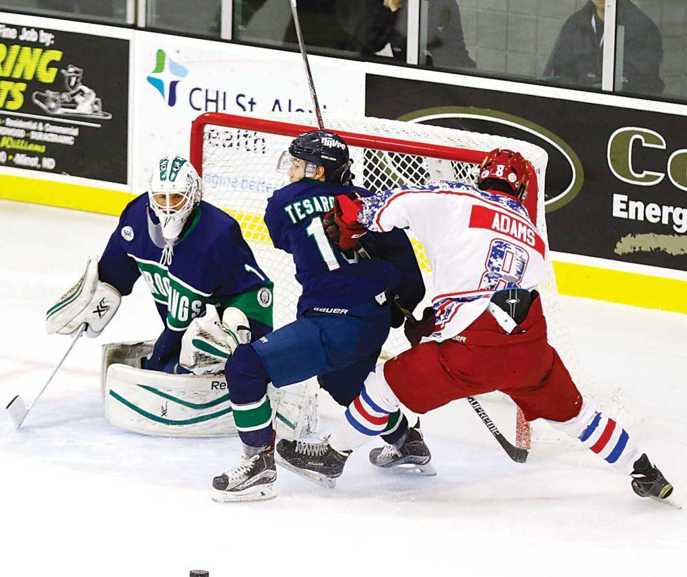 Photo courtesy of Steve Silseth  Minotauros forward Alex Adams (8) fights for position near the net during a junior league hockey game.