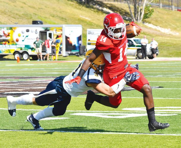 Garrick Hodge/MDN Minot State wide receiver Lavante Bushnell (14) shakes off a tackle during a college football game Saturday at Herb Parker Stadium in Minot.