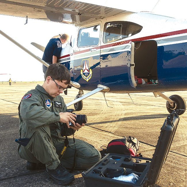 A Civil Air Patrol team from North Dakota is in Texas to assist in the aftermath of hurricane Harvey.  Casey DeVos, Bismarck, prepares his camera for aerial photography while Minot's Shawn Huizenga, background, completes a preflight inspection of a CAP aircraft.  Submitted Photo