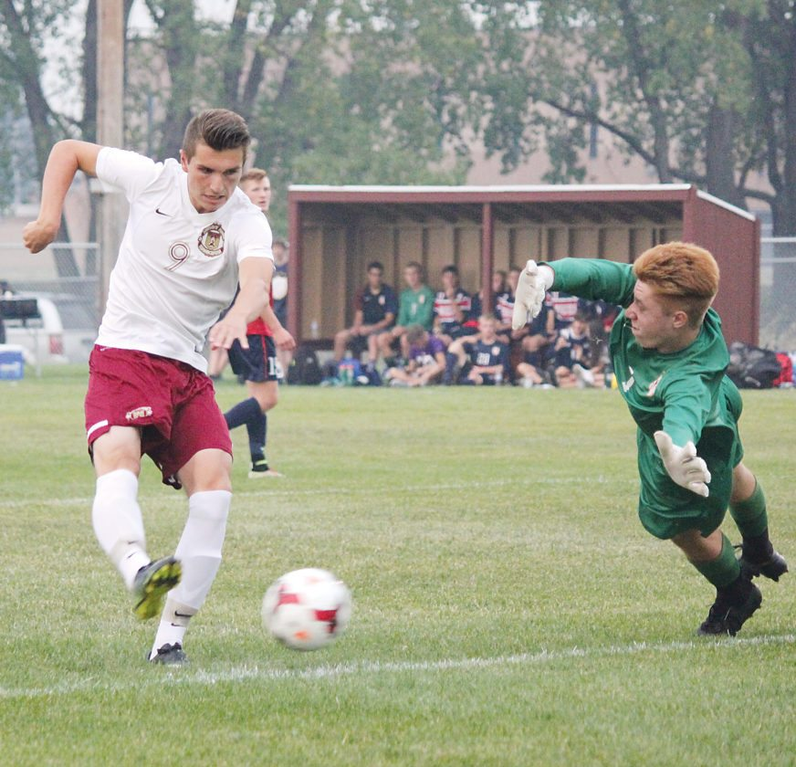 Alex Eisen/MDN Minot High senior Evan Bolinske (9) has his shot saved by Century goalkeeper Conor Fehr (green) in a West Region boys soccer game Tuesday at the Optimist Soccer Complex.