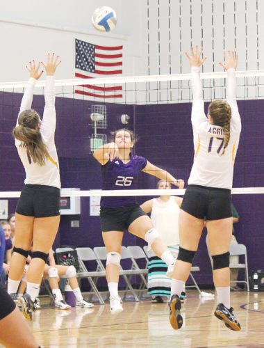 Alex Eisen/MDN Bishop Ryan junior Abbie McKay (26) hits the ball in between Velva blockers Greta Florence and Kaitlyn Lund (17) Tuesday in a Region 6 volleyball match at Bishop Ryan. Velva defeated Ryan 3-0.