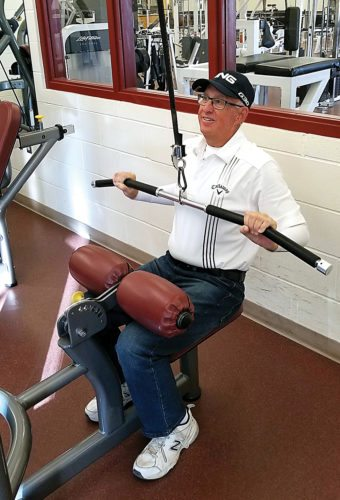 Submitted Photo Jeff Balentine, a cancer survivor and retired police officer, lifts weights in the Trinity Cancer Exercise Rehab program in Minot. The program is funded in part by the sales of T-shirts during the Minot Y's Men's Rodeo on October 5-8 at the State Fair Center. Photo courtesy of Russell Gust