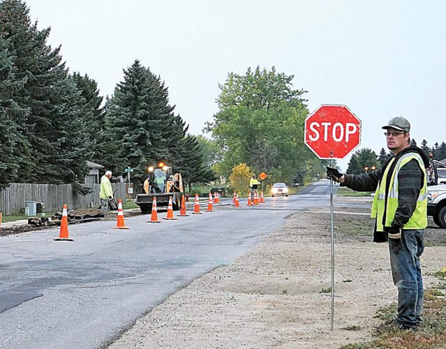 Jill Schramm/MDN City employees work on a patching job on the landfill road Thursday. The Minot City Council reduced employee pay raises for 2018 but left open the possibility of restoring the cuts.