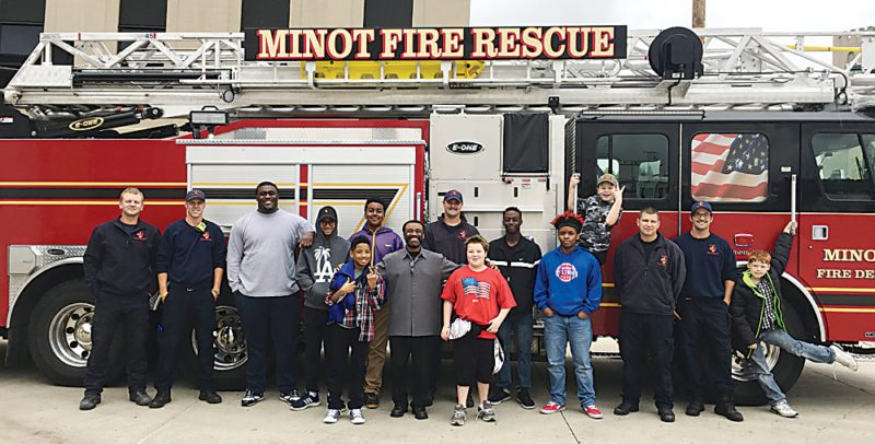 Shyanne Belzer/MDN Members of the Boys Club from Gospel Tabernacle and firefighters at Fire Station #2 in southeast Minot pose for a photo on Saturday during the club members' visit to the fire station.