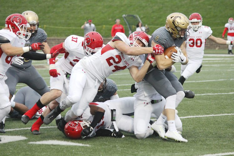 Sam Thiel/Marshall Independent Minot State freshman Lucas Butts (24) tries to drag down Southwest Minnesota State's Bailey Oslon (8) in a Northern Sun Intercollegiate Conference football game played Saturday evening in Marshall, Minnesota. SMSU beat Minot State 28-20.