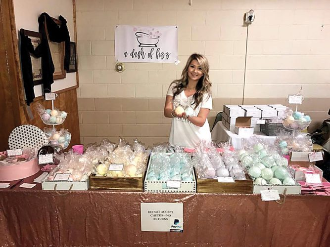 Submitted Photo Alexis Lee is shown with her booth at the Moose Lodge in Minot in May.